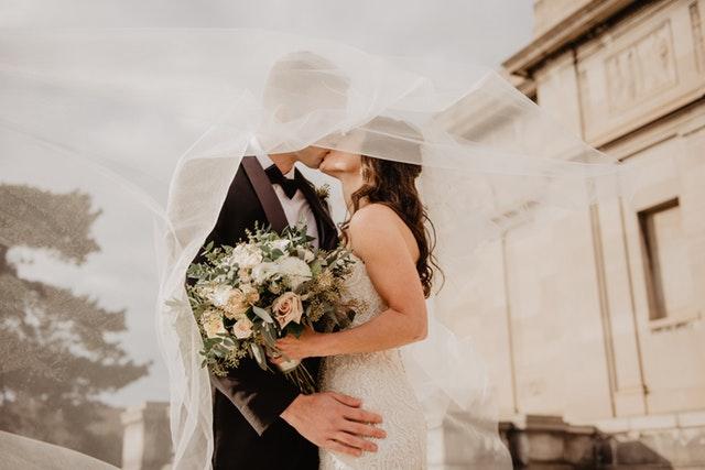 Nevesta a ženích bozkávajúci sa pod závojom