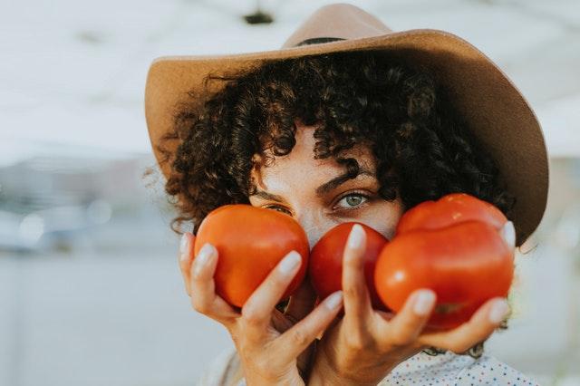 Žena držiaca červené paradajky