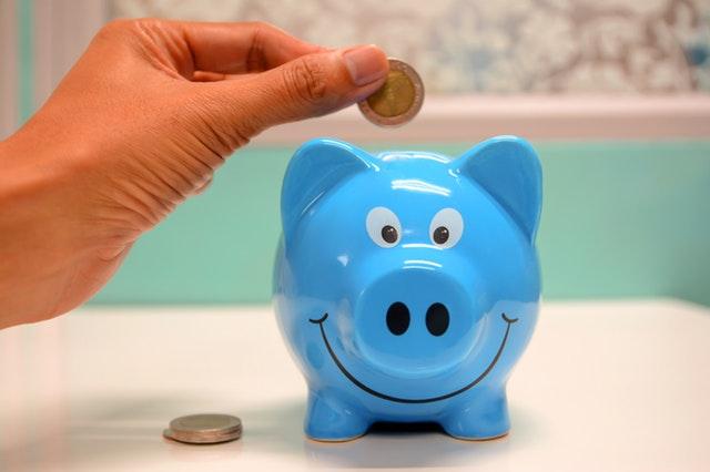 Pokladnička modré prasiatko, do ktorej človek vhadzuje peniaze
