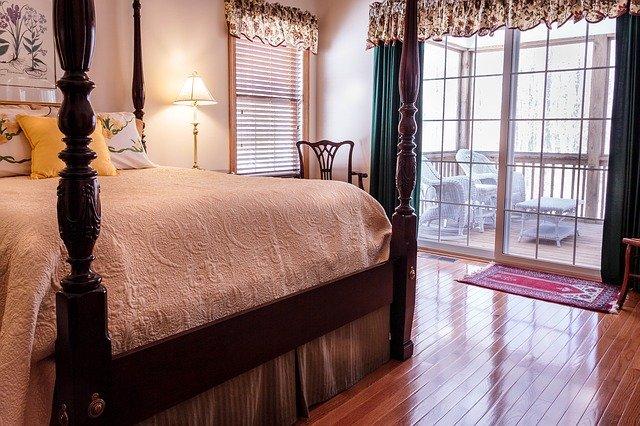 Spálňa s manželskou posteľou a veľkými sklenenými dverami vedúcimi na balkón.jpg