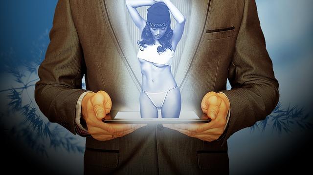 Muž drží v rukách tablet, z ktorého vychádza sexy žena