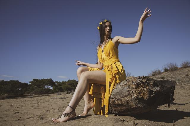 Žena v žltých šatách sedí na skale v púšti