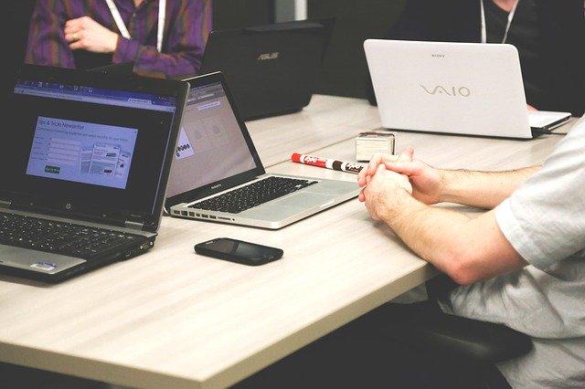 Dvaja muži sedia v kancelárii pri počítačoch